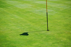 Flag shadow on the golf field Stock Photography