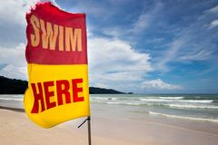 Flag with sign swim here at the beach for inform to tourist for safety area where safe to swim. summer beach at phuket , thailand. Security , safety and rescue stock photo