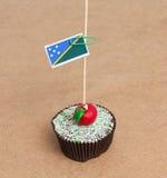 Flag of Solomon Islands on cupcake. On wood background royalty free stock image