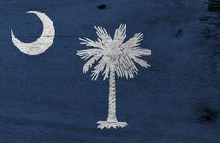 Flag of South Carolina on wooden plate background. Grunge South Carolina flag texture.
