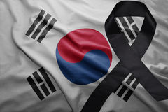 Flag of south korea with black mourning ribbon. Waving national flag of south korea with black mourning ribbon stock photo