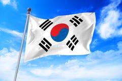 Flag of South Korea developing against a blue sky. Flag of South Korea developing against a clear blue sky stock photo