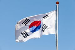 Flag of South Korea over blue sky. Flag of South Korea, also known as the Taegukgi waving on a flagpole over blue sky background royalty free stock image