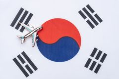 Flag of South Korea and the plane. The concept of travel. Toy airplane on South Korea flag stock images