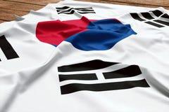 Flag of South Korea on a wooden desk background. Silk South Korean flag top view.  stock photo