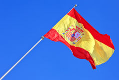 Flag of Spain flying in the wind against a blue sky Stock Photo