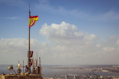 Flag of Spain on a tower of the fortress of Santa Barbara in Alicante. ALICANTE, SPAIN - SEPTEMBER 9, 2014: Developing the flag of Spain, mounted on a tower of Stock Images
