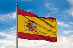 Flag of Spain waving in the wind against white cloudy blue sky. Spanish flag royalty free stock photo