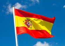 Flag of Spain waving in the wind on flagpole against the sky with clouds on sunny day. Close-up stock photos