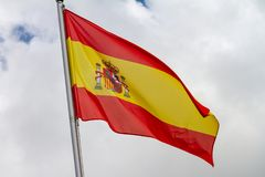 Flag of Spain waving in the wind on flagpole against the sky with clouds on sunny day. Close-up royalty free stock photo