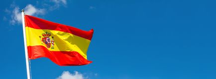 Flag of Spain waving in the wind on flagpole against the sky with clouds on sunny day. Banner, close-up royalty free stock photos