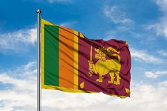 Flag of Sri Lanka waving in the wind against white cloudy blue sky. Sri Lankan flag stock photo
