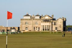 Flag - St Andrews Old Course. The flag on the 17th hole of the Old Course on the St Andrews links, with the Royal and Ancient clubhouse in the background stock image