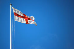 Flag of St George. St George flag with flag pole wind blown showing motion against a blue sky background Stock Photography
