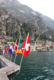 Flag states over the typical Italian style buildings, the city of Limone. Under the mountains Stock Images