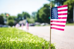 Flag on street curb in a neighborhood for 4th of July Celebration stock image