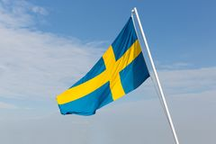 Flag of Sweden blowing in the wind. With a blue sky background Stock Images