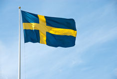 Flag of Sweden in the blue sky. Swedish flag waving in the blue sky on a sunny day Royalty Free Stock Images