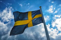 Flag of Sweden with blue sky and clouds at the background Stock Photography