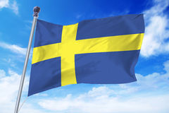 Flag of Sweden developing against a clear blue sky Stock Photos