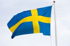 Swedish flag waving in the wind. The flag of Sweden is the national flag of the Kingdom of Sweden. It consists of a yellow or gold Nordic Cross on a field of Stock Image