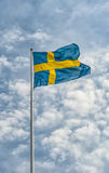 Flag of Sweden. A Swedish flag waving in the wind against a beautiful summer sky Royalty Free Stock Photo
