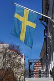 Flag of Sweden waving above the balcony of a building. Blue sky behind Royalty Free Stock Images