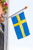 Flag of Sweden. Waving above the balcony of a building, blue sky behind Stock Photo