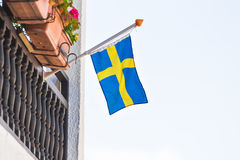 Flag of Sweden. Waving above the balcony of a building, blue sky behind Royalty Free Stock Image