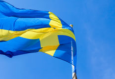 Flag of Sweden waving in the wind on a blue sky. Background Royalty Free Stock Photo