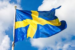 Flag of Sweden with yellow cross waving in the wind. Against a blue sky background with clouds Stock Photos