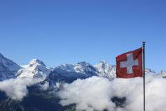 Flag of Switzerland against Swiss Alps. Switzerland flag against the backdrop of the Swiss mountains with copyspace Royalty Free Stock Photo