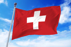 Flag of Switzerland developing against a clear blue sky Stock Images