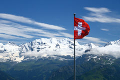 Flag of Switzerland with snowy mountains. The flag of Switserland with a lot of snowy mountains in the background Royalty Free Stock Image