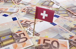 Flag of Switzerland sticking in euro notes. Stock Image