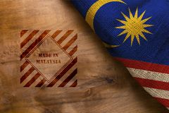 Flag and symbol made in Malaysia. On a wooden surface royalty free stock photos