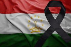 Flag of tajikistan with black mourning ribbon. Waving national flag of tajikistan with black mourning ribbon Royalty Free Stock Image