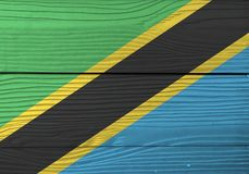 Flag of Tanzania on wooden plate background. Grunge Tanzanian flag texture. stock illustration