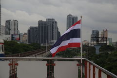 Flag of Thailand waving in front of modern buildings in Bangkok. Bangkok is the capital of Thailand and in this photo some modern buildings as well as Thailand`s stock image