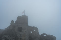 Flag on top of medieval castle ruin in heavy fog Royalty Free Stock Image