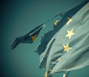 Flag is torn off at side, symbol of problems, decay, disintegration, decomposition, breakdown. European union twelve star flag torn and with knots in wind on stock images