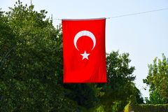 Flag of Turkey. Flag of Turkey against a background of green leaves and sky royalty free stock images