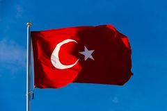 Flag of Turkey on flagpole waving in the wind against the blue sky Royalty Free Stock Image