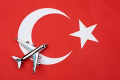 Flag of Turkey and the plane. The concept of travel. Toy airplane on the Turkish flag Stock Image