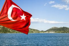 The flag of Turkey. Turkish flag on a background of the sea coast royalty free stock images