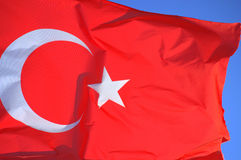 Flag of Turkey. Waving flag of Turkey closeup blowing in the wind on blue sky background royalty free stock photography