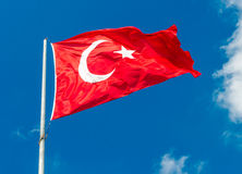Flag of Turkey. Waving flag of Turkey over blue sky background stock image
