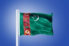 Flag of Turkmenistan flying against a blue sky Royalty Free Stock Photography