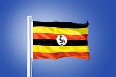 Flag of Uganda flying against a blue sky Royalty Free Stock Photo