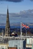 UK flag flying in front of the spire of the Tron Kirk in Edinburgh. Flag of the UK flying in front of the spire on the Tron Kirk in Edinburgh, Scotland Stock Photo